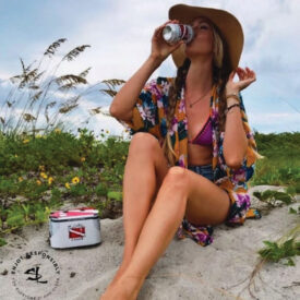 Salt Life Lager woman on beach drinking from can